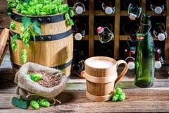 La cerveza sirvió en una taza de madera en el sótano Fotografía de archivo
