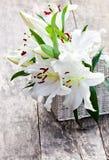 La cesta blanca con el lirio blanco florece el ramo en t de madera rústico Imágenes de archivo libres de regalías