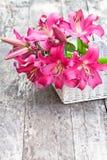 La cesta blanca con el lirio rosado florece el ramo en etiqueta de madera rústica Imagen de archivo libre de regalías