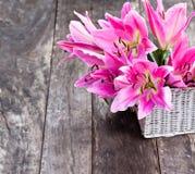 La cesta blanca con el lirio rosado florece el ramo en TA de madera rústica Imagenes de archivo