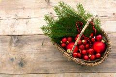 La cesta con las chucherías y el pino rojos de la Navidad ramifica desde arriba de o Fotografía de archivo libre de regalías