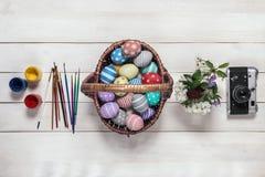 La cesta con los huevos de Pascua coloridos, pintados en hecho a mano, ramo de flores de la primavera, las pinturas, los cepillos Imagen de archivo