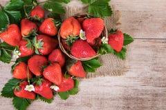 La cesta de fresas frescas con las hojas en la opinión superior del fondo del vintage de la fresa madura da fruto Fotografía de archivo