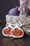 La cesta de higo da fruto con las mitades una en una tabla imagenes de archivo