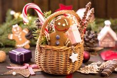 La cesta de la diversa Navidad trata, hombre de pan de jengibre en la tabla Foto de archivo libre de regalías