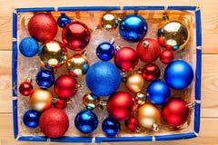 La cesta de la paja embaló por completo de bolas multicoloras de la Navidad Imagenes de archivo