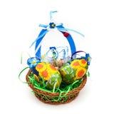La cesta de mimbre con pascua pintó los huevos Imagen de archivo libre de regalías