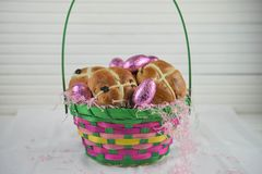La cesta de Pascua llenó de los bollos cruzados calientes frescos y de los huevos rosados brillantes Imagen de archivo libre de regalías