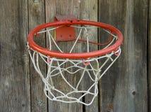 La cesta del baloncesto atada a una cerca de madera sube fotos de archivo