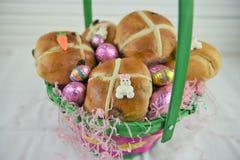 La cesta linda de Pascua llenó de los bollos cruzados calientes y de los huevos de Pascua frescos Fotos de archivo