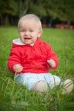 La chéri émotive s'asseyent sur l'herbe verte photos libres de droits