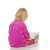La chéri adorable s'asseyent avec l'ordinateur de tablette sur le blanc Images libres de droits