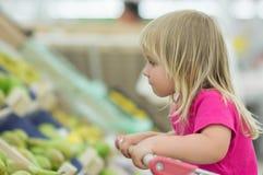 La chéri adorable s'asseyent dans le chariot dans le supermarché Photo libre de droits