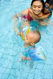La chéri apprennent à nager avec la maman Photos stock