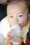 La chéri asiatique est lait de consommation Photos stock