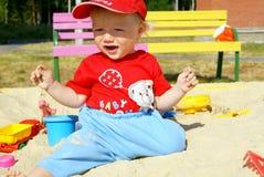 La chéri heureuse dans un bac à sable Photographie stock libre de droits