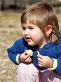 La chéri mange du pain photo stock
