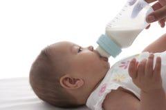 La chéri obtient allaitante au biberon Image stock