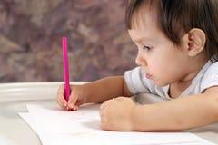 La chéri s'asseyant à la table et dessine image stock