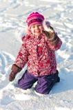 La chéri s'assied sur la neige et le sourire Image libre de droits
