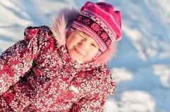 La chéri s'assied sur la verticale de neige Photographie stock