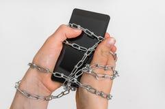 La chaîne attache ensemble les mains et le smartphone - concept de dépendance photos libres de droits