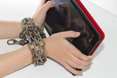 La chaîne de fer attache ensemble les mains et le smartphone - concept de dépendance de téléphone portable images stock