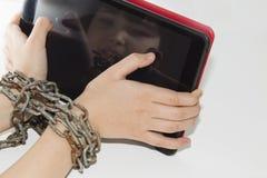 La chaîne de fer attache ensemble les mains et le smartphone - concept de dépendance de téléphone portable images libres de droits