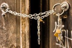 La chaîne en métal ferme une vieille porte d'une maison abandonnée photo stock