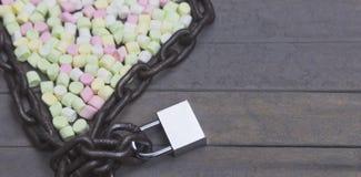 La chaîne et la serrure ont arrangé avec la guimauve pour Valentine Day dans la forme de coeur sur le bois Photographie stock libre de droits