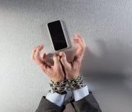 La chaîne tendue a attaché l'otage de mains d'homme d'affaires du burn-out mobile image stock