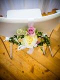 La chaise du ` s de jeune mariée est décorée des fleurs images stock