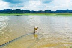 La chaise est dans l'eau Photographie stock libre de droits