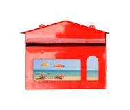 La chaise et le parapluie de plage sur le sable échouent dans la boîte aux lettres rouge sur le fond blanc, Photo stock