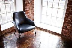 La chaise se tient près d'une fenêtre sur le fond de mur de briques dans W Photos libres de droits