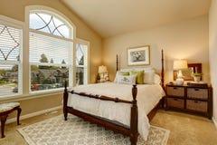 La chambre à coucher beige confortable avec le plafond voûté et le style victorien élégant enfoncent Images stock