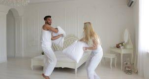 La chambre à coucher de combat d'oreillers de couples mélangent la femme d'homme de course jouant ayant l'amusement ensemble banque de vidéos