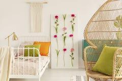 La chambre à coucher de la fille conçue dans le style de boho, le panneau de fleur et la macramé sur le mur, chaise de paon dans  images libres de droits