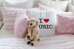 La chambre à coucher de l'enfant avec la poupée et les oreillers roses sur le lit Photos stock