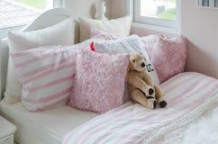 La chambre à coucher de l'enfant avec la poupée et les oreillers roses sur le lit Photographie stock libre de droits