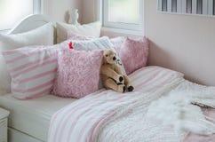 La chambre à coucher de l'enfant avec la poupée et les oreillers roses sur le lit Photographie stock