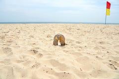 La chancleta en la arena y la seguridad señala la muestra por medio de una bandera en la playa Fotos de archivo