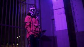 La chaqueta y las gafas de sol rojas que llevan masculinas jovenes enérgico canta en la noche almacen de metraje de vídeo