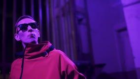 La chaqueta y las gafas de sol rojas que llevan masculinas lindas enérgico canta en la noche almacen de metraje de vídeo
