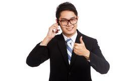 La charla asiática de la sonrisa del hombre de negocios sobre la demostración del teléfono móvil manosea con los dedos para arrib Imagenes de archivo