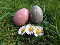 La chasse à oeuf de pâques eggs dans l'herbe avec des daisys photos stock