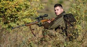 La chasse est passe-temps masculin brutal Fusil de prise de chasseur L'homme portent le fond de nature de v?tements de camouflage photo libre de droits