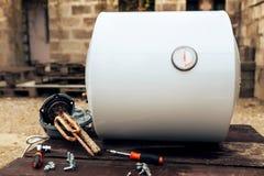 La chaudière a démonté, se trouvant à côté de l'élément de chauffe, des écrous et des outils sur la surface en bois, dehors photo stock