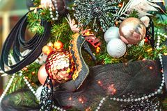 La chaussure à talons hauts de Madame accroche sur un arbre de Noël décoré des jouets photos stock