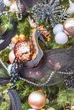 La chaussure à talons hauts de Madame accroche sur un arbre de Noël décoré des jouets et des guirlandes photos stock